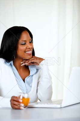 Pretty young woman smiling and reading on laptop