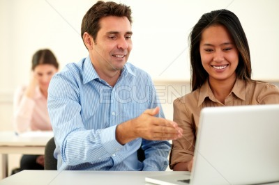Professional man and woman working on laptop