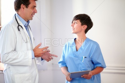 Professional medical couple standing and speaking