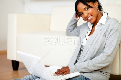 Relaxed woman smiling at you with a laptop