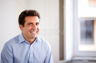 Satisfied hispanic businessman smiling at you