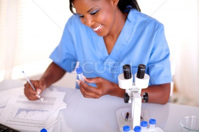 Scientific female working with test tube and notes