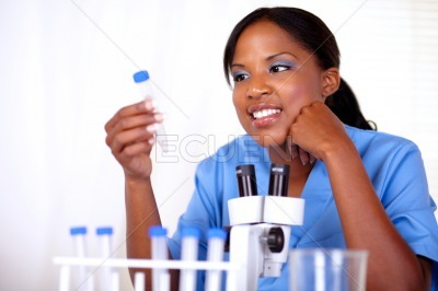 Scientific woman holding and looking to test tube