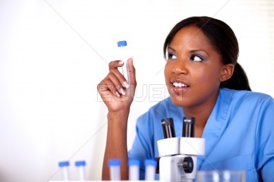 Scientific woman looking right holding test tube