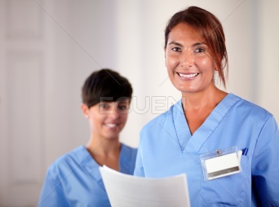 Senior and young nurse smiling at you