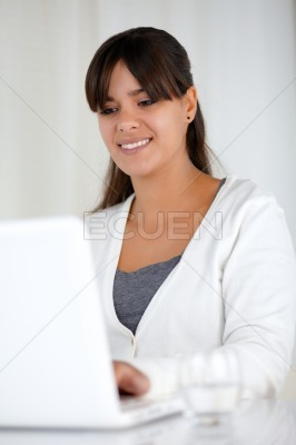 Smiling young female working with laptop computer