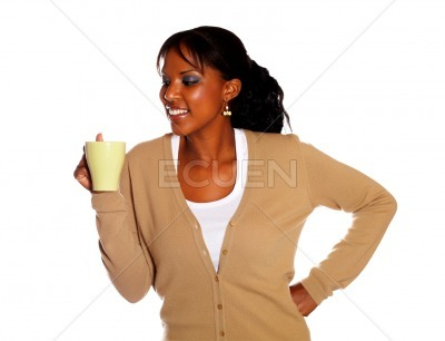 Smiling young woman looking to her mug