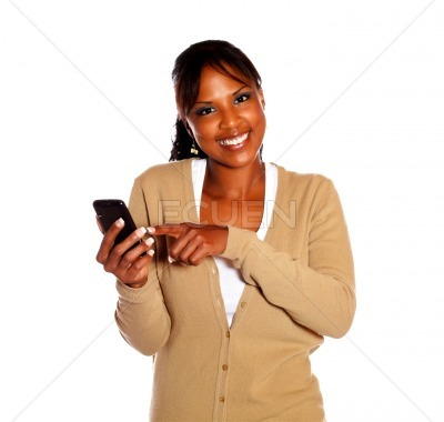 Smiling young woman sending message by cellphone