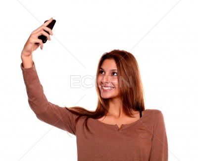 Smiling young woman taking a photo with cellphone