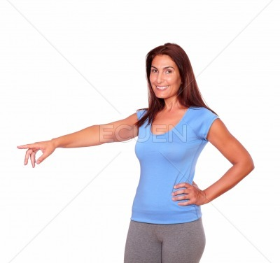 Sporty adult woman in gym clothing pointing right