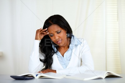 Stressed young black woman reading a book