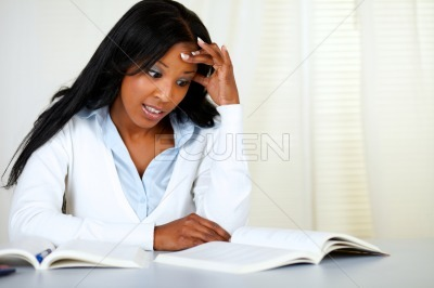 Stressed young black woman studying