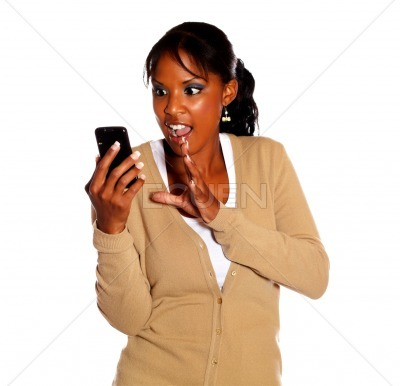 Surprised ethnic woman reading a message on phone