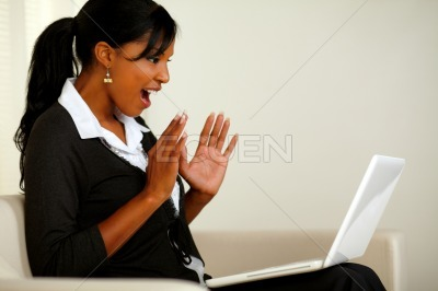 Surprised young woman reading great news on laptop