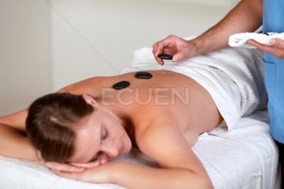 Woman relaxing while having a hot stone massage