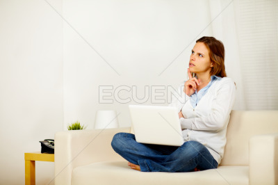 Young adult woman thinking on sofa with a laptop