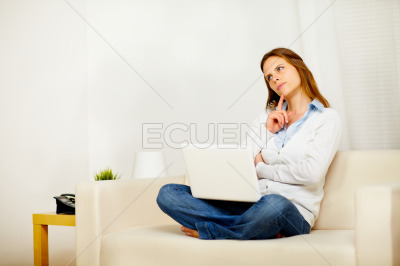 Young attractive woman thinking on sofa with a laptop