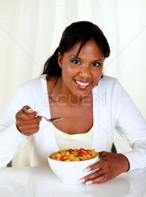 Young lady smiling at you and having breakfast