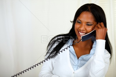 Young lovely female conversing on phone