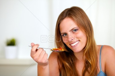 Young lovely woman eating breakfast