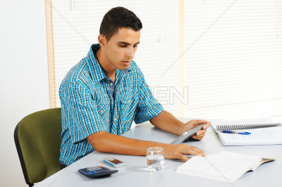 Young man studying with a tablet PC