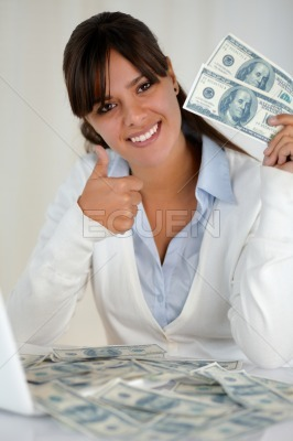 Young woman looking at you holding cash dollars