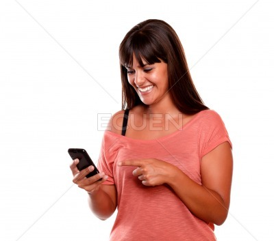 Young woman pointing and looking to mobile