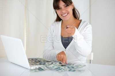 Young woman pointing at you with cash money
