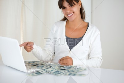 Young woman pointing laptop screen with cash money