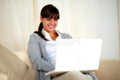 Young woman sitting on sofa and working on laptop