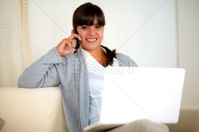 Young woman speaking on cellphone sitting on sofa
