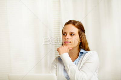 Young woman thinking in from laptop