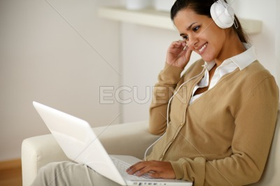 Young woman with headphone reading laptop screen