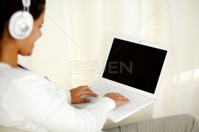 Young woman working on laptop listening music