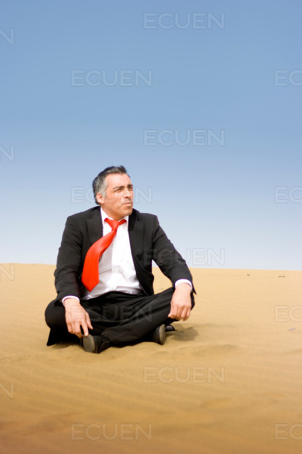 A business man relaxing and sit down on the sand of the desert stock photo