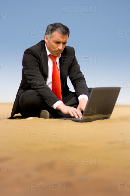 A business man relaxing and sit down on the sand of the desert a stock photo