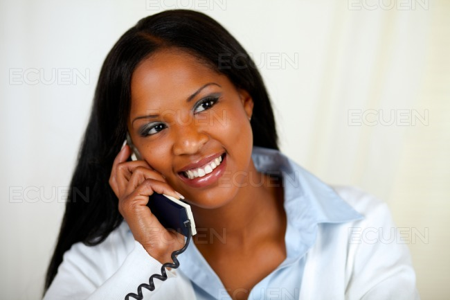 African woman conversing on phone stock photo