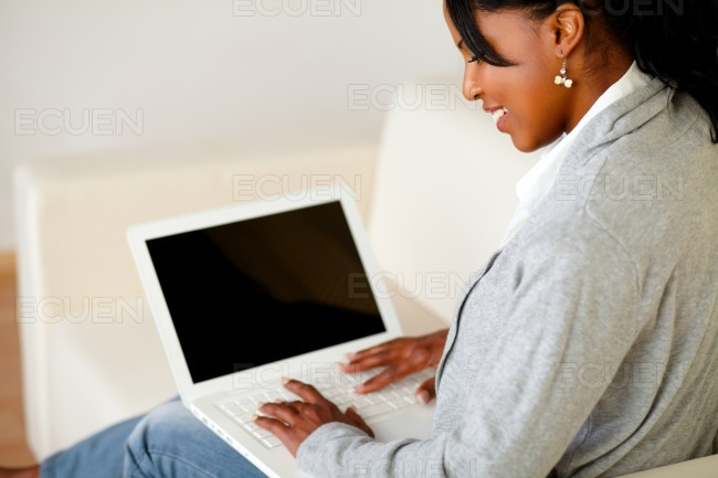 Afro-american girl browsing the internet on laptop stock photo