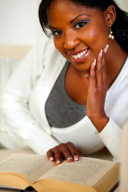 Afro-american lady smiling and reading a book stock photo