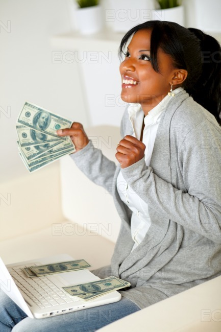 Afro-american woman looking up with dollars stock photo