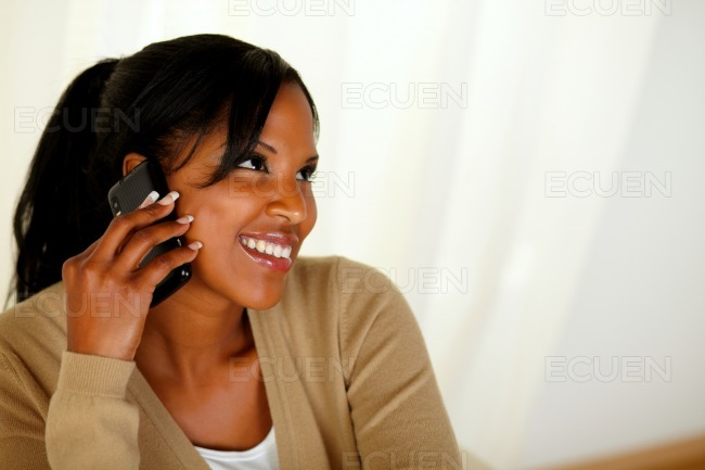 Afro-american young woman conversing on cellphone stock photo