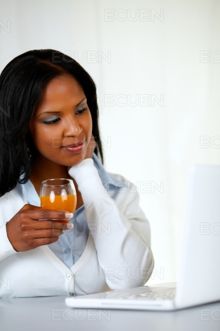 Afro-american young woman drinking orange juice stock photo