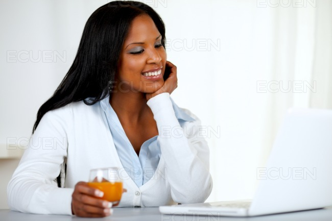 Afro-american young woman looking to laptop screen stock photo