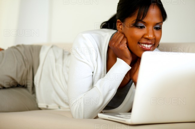 Afro-american young woman reading on laptop screen stock photo