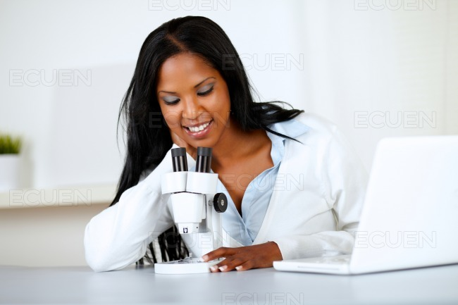 Attractive african woman working with a microscope stock photo