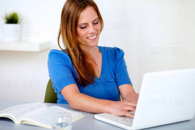 Attractive blonde woman learning on laptop stock photo