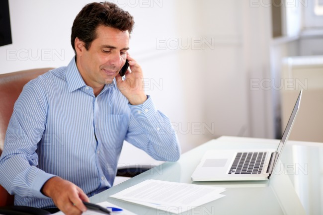 Attractive businessman talking on his cellphone stock photo