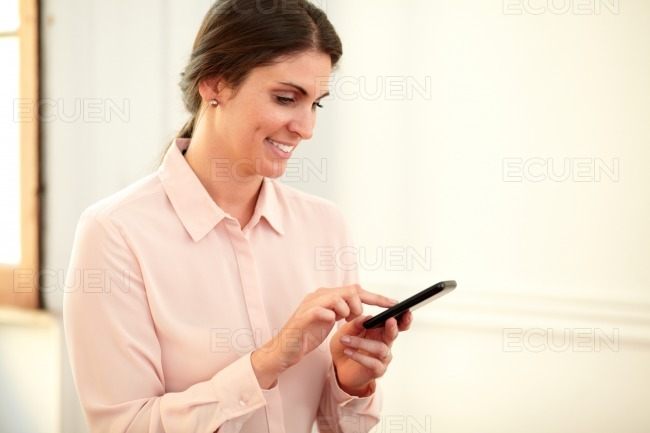Attractive caucasian woman texting with her mobile