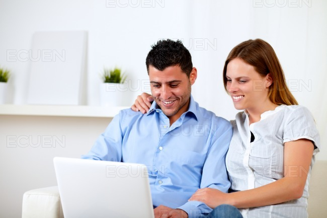 Attractive couple smiling and looking to computer stock photo