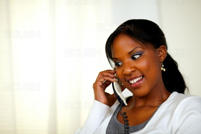 Attractive female smiling and conversing on phone stock photo
